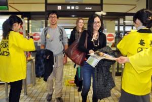 奄美空港に到着してシマ博のパンフレットを受け取る観光客=30日、奄美市笠利町