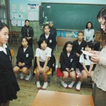 母からのメッセージに聞き入る泉沙葉羅さん(左)=19日、奄美市名瀬の小湊小