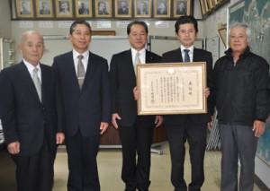 伊集院村長(中央)から表彰状を伝達されたやまと学校応援団関係者ら=9日、大和村役場