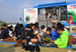 キャラバンカーの周りで思い思いに読書を楽しむ児童ら=10日、伊仙町の鹿浦小学校