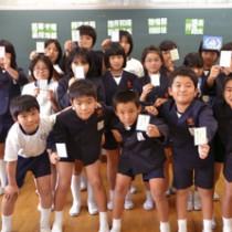 自分が描いたイラストのある札を持つ5年生と竹村さん(左)=16日、与論町の与論小学校