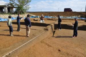 グスク時代初期の水田跡などの遺構が確認された前当り遺跡=24日、伊仙町面縄 (下)土坑墓から出土した全長約30㌢の鉄刀