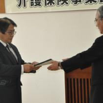 第6期計画を朝山市長に答申する稲委員長(左)=10日、奄美市役所