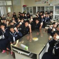 修学旅行で交流した七城中から届いた特産米でおにぎりにした龍南中の2年生と保護者ら=3日、龍郷町