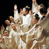 アマミ舞で祖母の半生を表現する花柳さん(中央)=21日、龍郷町りゅうゆう館