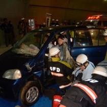 訓練で事故車両のドアをこじ開けて負傷者を救出する消防隊員ら=24日、瀬戸内町の網野子トンネル