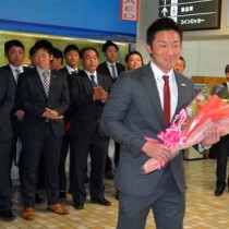 歓迎の花束を受け取るパナソニック野球部の松元主将=2日、奄美空港