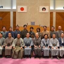 大島紬の着物姿で本会議に出席し、記念撮影する伊藤祐一郎知事と21人の県議ら=25日、県議会庁舎(県議会事務局提供)
