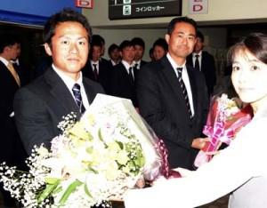 歓迎の花束を受け取る和嶋監督と渡邉貴美男主将(写真奥から)=13日、奄美空港