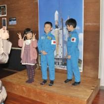 宇宙飛行士の訓練着を試着する参加者=11日、奄美少年自然の家