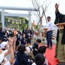子どもたちに豆をまく武蔵川親方と三崎さん=3日、瀬戸内町