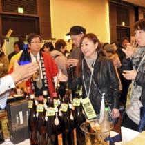 来場者に黒糖焼酎の特徴を説明する蔵元担当者=4日、福岡市のソラリア西鉄ホテル