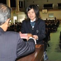 贈呈式で松田清藏理事長(左)から本を受け取る作南々帆さん=27日、徳之島高校