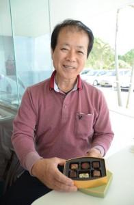 自社製品が原料に採用されたチョコレート商品を手にする松山社長