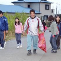 マラソンコース沿いのごみを拾う参加者=22日、与論島