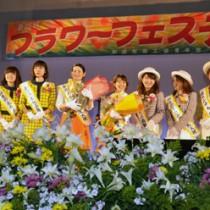 2015年度おきのえらぶ島観光大使として紹介される森さんと島田さん(右から5番目と6番目)=15日、和泊町民体育館