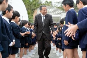 お別れの握手を交わす村野校長と児童ら=27日、奄美小学校