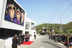 加計呂麻島展示・体験交流館が落成。諸鈍シバヤ巨大壁画の除幕式=23日、瀬戸内町