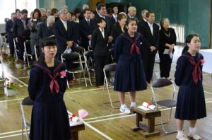 校歌を斉唱する(前列右から)須田さんと橋口さん。卒業式には大勢の住民が駆け付けた=13日、瀬戸内町の薩川中