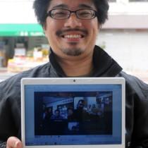 喜界島とイランの人々がインターネット上で対面した様子が映し出されたパソコンを手にする東さん=21日、奄美市名瀬