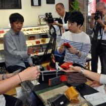 大島紬を使った小物を見せて助言を受ける川畑さん(左)=19日、奄美市名瀬