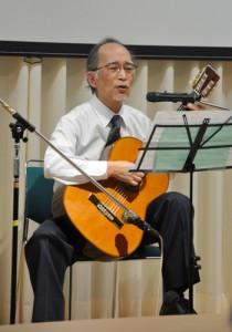講演終了後に自作の歌を披露する古川医師=14日、奄美市名瀬