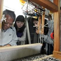 大島紬の機織りを見学するゼミ生=6日、本場奄美大島紬専門学院