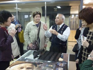 紬の魅力について説明を受けるツアーの一行=2月6日、紬会館