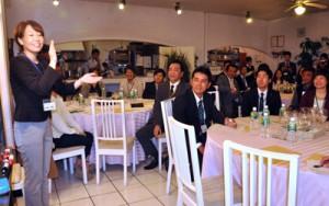 大司さん(左)の指導で笑顔のつくり方を学ぶ受講生=25日、奄美市名瀬の飲食店アガルイ