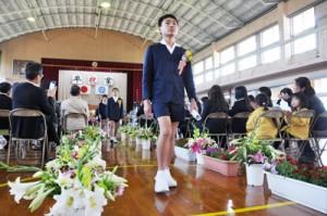 多くの花で彩られた式場を後にする卒業生=24日、知名町の住吉小学校体育館
