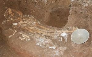 洞窟内の地中から見つかった人骨と青磁碗