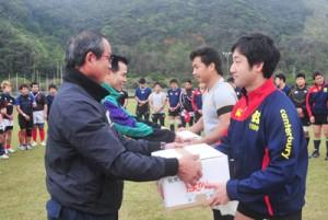奄美合宿を終えたイレブンにタンカンを贈る奄美ラグビー連盟の関係者(左)=7日、同