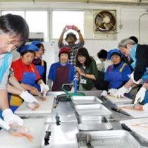 漁師の妻らの手ほどきを受けて魚をさばくツアー参加者=14日、奄美市笠利町