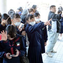 自分の番号を撮影するなど、合格を喜ぶ受験生たち=13日、奄美市名瀬の大島高校