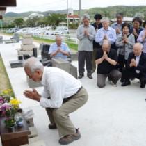 区画整理された新たな墓地の一角で仮納骨堂に手を合わせる会員=5日、龍郷町浦