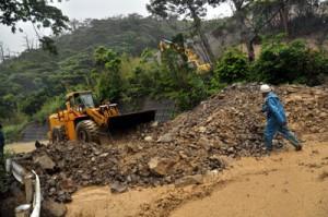 大雨によって採石場の土砂が流出し市道を埋めた現場=12日午前9時35分、奄美市住用町市
