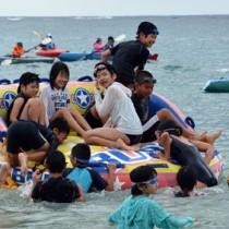 海開きでマリンスポーツを楽しむ赤木名小の児童ら=21日、笠利町用安海岸