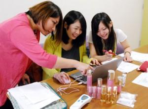 奄美市内の事業所で働くインターンシップ生たち(右2人)=2014年撮影