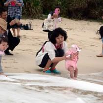 無病息災を祈って海水に子どもの足を浸す母親たち=21日、奄美市名瀬の大浜海浜公園