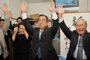 トップ当選を決め支援者らと万歳三唱する永井章義氏=12日午後10時08分、奄美市名瀬井根町
