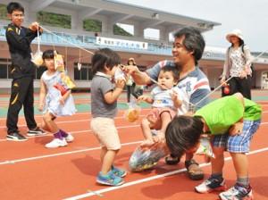保護者とパン食い競争を楽しむ子どもたち=26日、名瀬運動公園陸上競技場