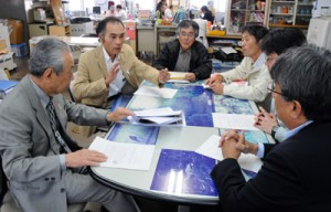 市地区で発生した土砂流出現場の状況などを市役所担当者に説明する栄さん(左から2人目)ら=14日、奄美市役所