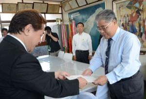 伊地知町長(右)へ新庁舎建設基本構想案を答申する前委員長=27日、和泊町長室