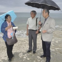 砂が激減し、ビーチロックがむきだしになった海岸の状況を調べる向井代表(中央)と安部さん(左)=28日、奄美市の大浜海浜公園