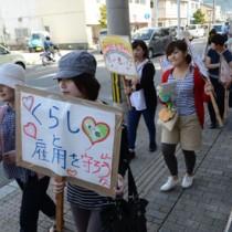 平和や労働者の権利などを訴えながらデモ行進する参加者=1日、奄美市