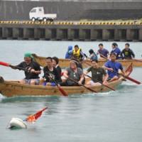 あいにくの天候にも負けず熱戦を繰り広げた舟こぎ大会=24日、瀬戸内町の与路港