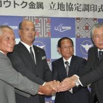 協定書に調印後、握手する勝山弘行社長(右から2人目)と徳田康光町長(同3人目)=27日、龍郷町役場