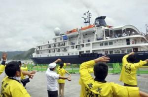 観光関係者の見送りを受けて名瀬港を離れるカレドニアンスカイ=14日、奄美市名瀬