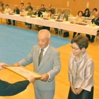 高岡秀規町長から表彰状を受け取る金婚夫婦=25日、徳之島町