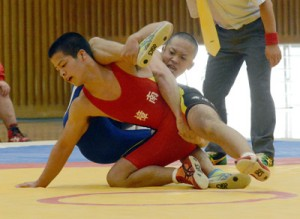 60㌔級、決勝進出を懸けた2回戦で岩佐那由汰(鹿屋中央)の攻めを耐える武田海喜(樟南)=20日、樟南高校